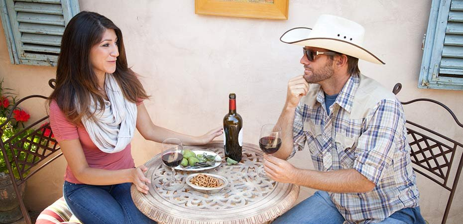 A couple at a side street cafe enjoying a meal with wine