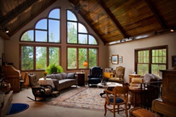 Living room with large vaulted ceiling and full wall window