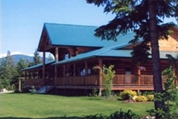 Large log cabin with wrap-around porch in field