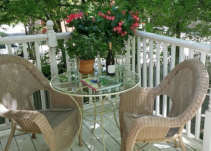 Balcony with wicker chairs and glass table