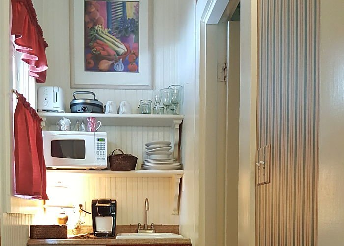 A kitchenette with microwave, sink, and coffee machine