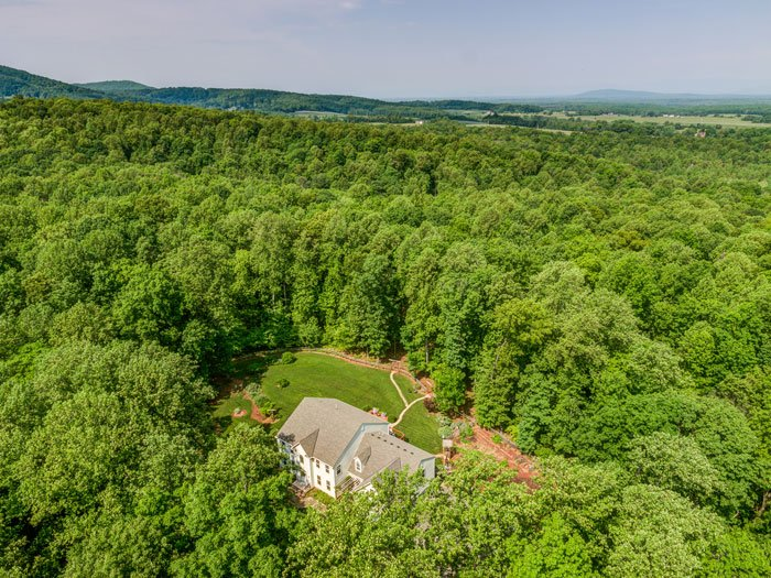 Aerial view of Uphill House surrounded by forest