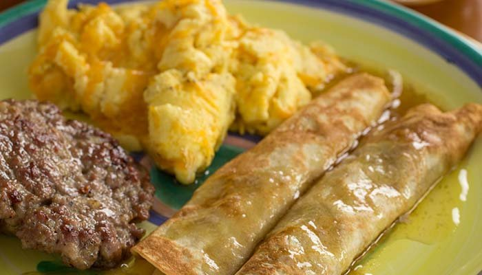 Thin rolled pancakes, with scrambled eggs and sausage patties