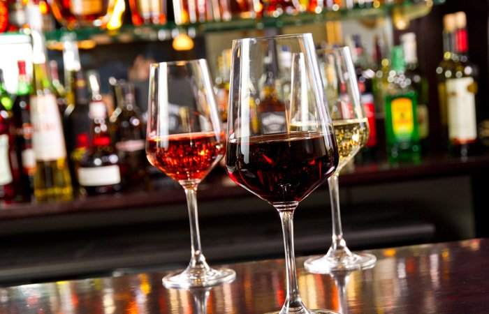 Three glasses of wine sitting on a bar top