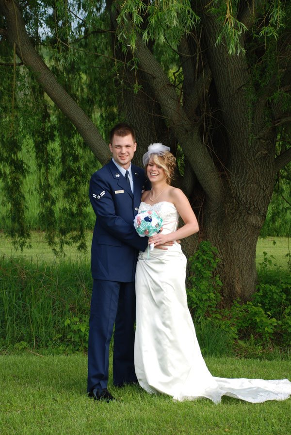Newlywed couple standing under a willow tree