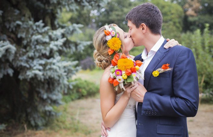 Couple kissing while holding a bouquet together