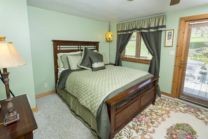 A queen bed in a green themed room