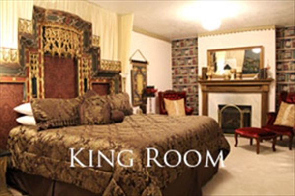 King-sized bed with large headboard next to a fireplace