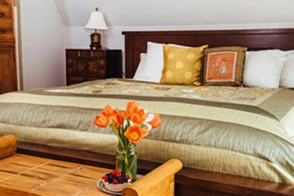 King-sized bed with footstool and vase with flowers