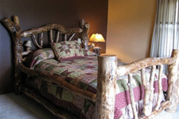 Decorative log framed bed next to a lamp