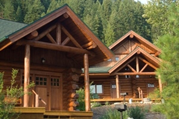 Trees around log cabins with roofed porches