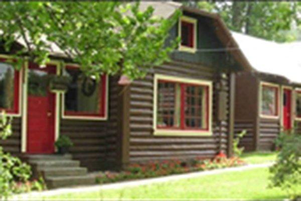 Painted log cabins along sidewalk
