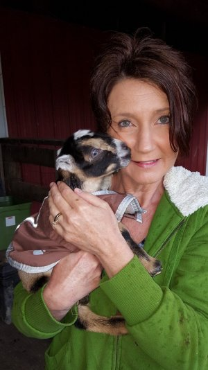 A woman holding a baby goat close to her