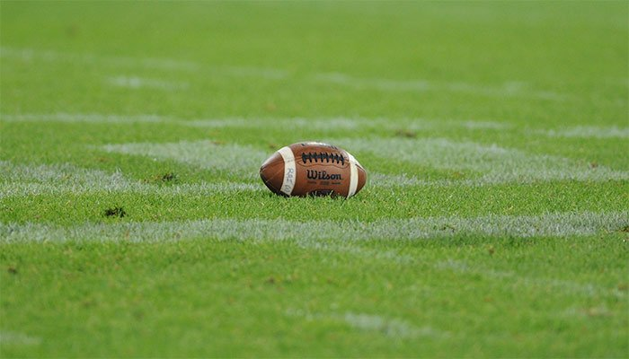 An American football on a grass field