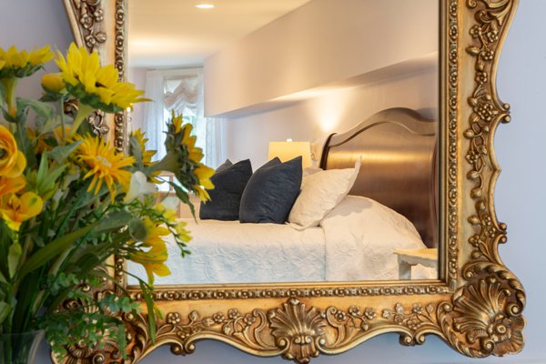 Bed reflection in a gilded frame mirror