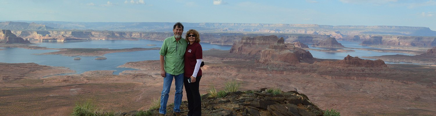 A couple standing on the edge of a butte