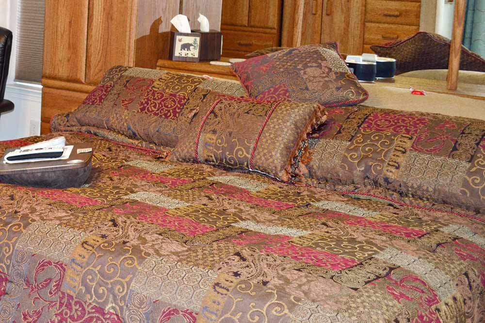 A bed with earth-toned covers