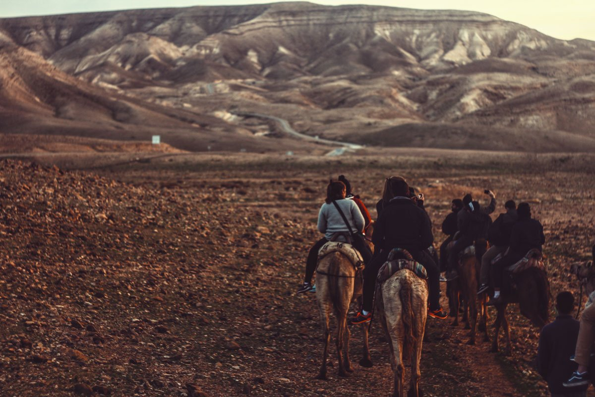 a group of horseback riders in the hills