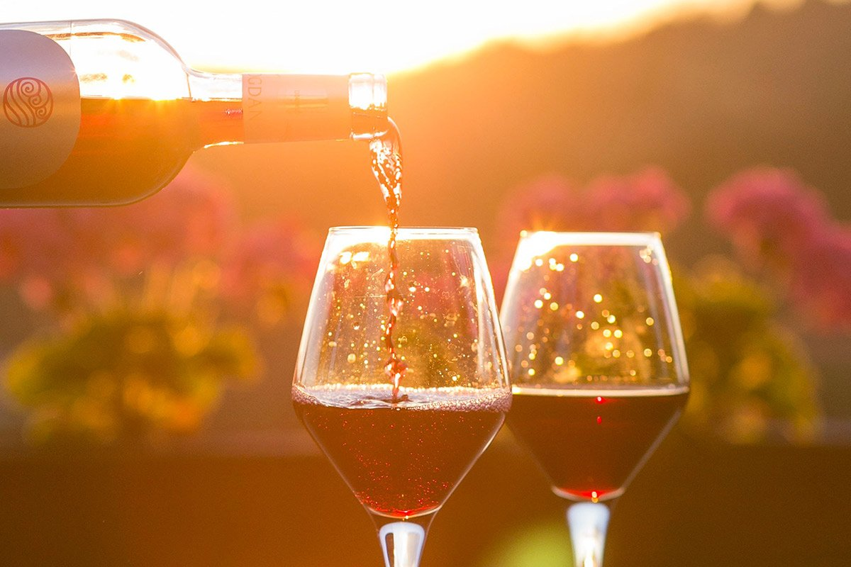pouring wine into glasses with sunset