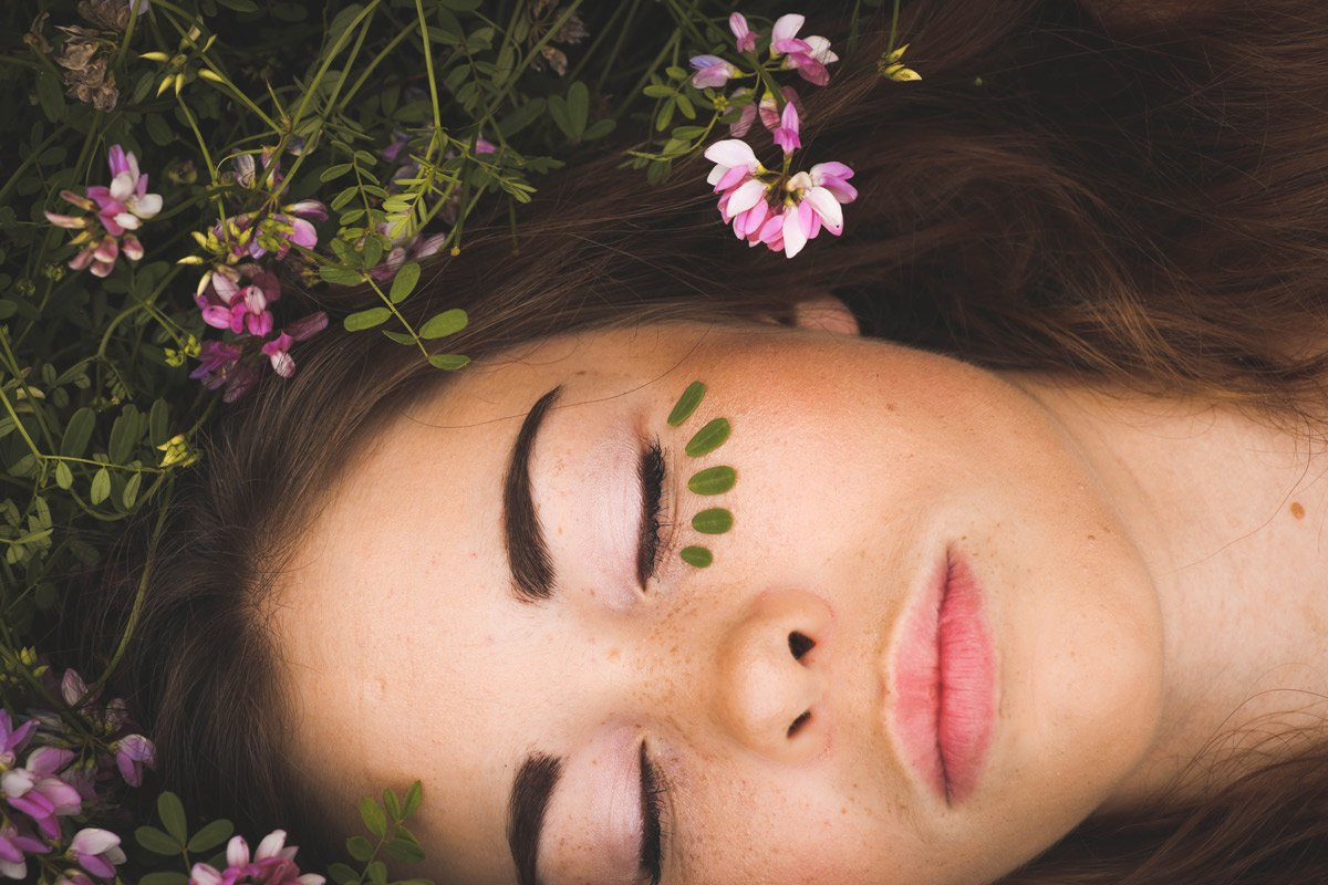 woman laying down with leaves around her eye