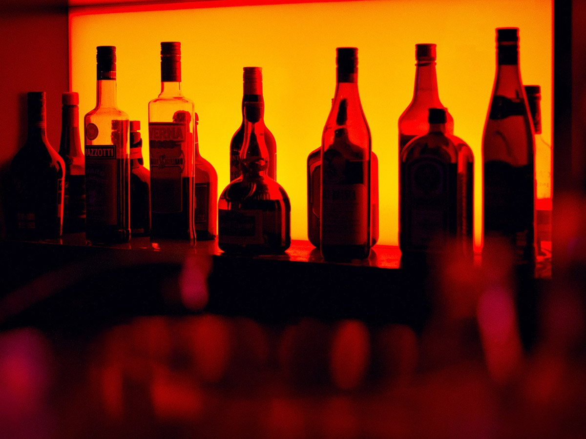 liquor bottles against a lit backdrop