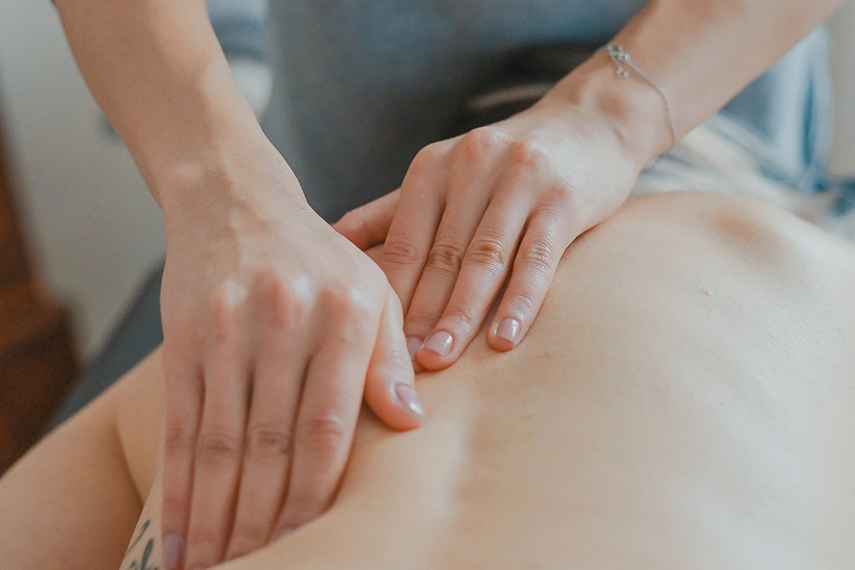 hands massaging a bare back