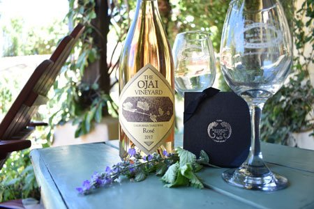 A bottle of wine with two glasses and a gift certificate