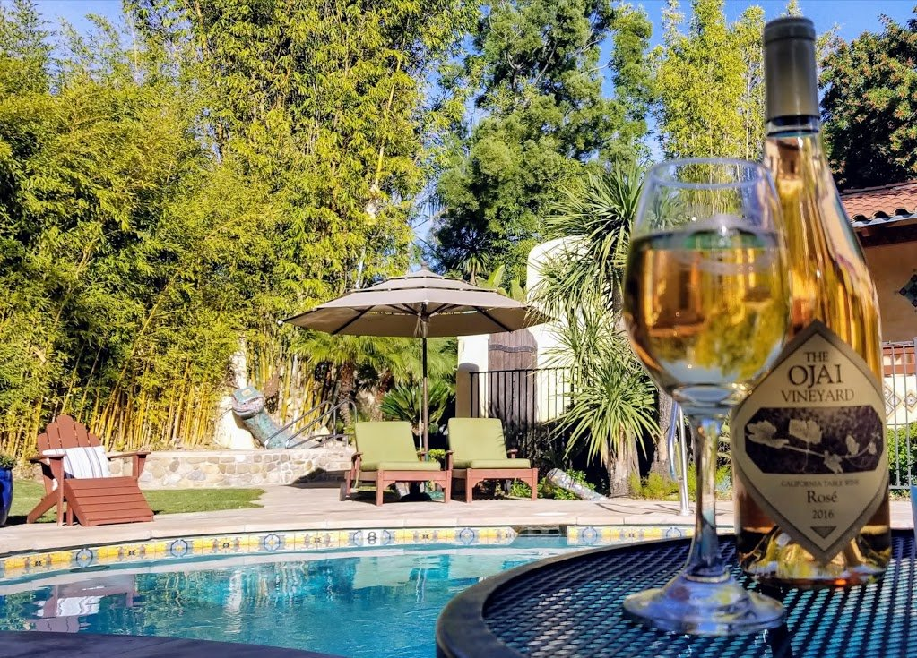 A bottle and glass of wine near a swimming pool