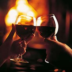 Two wineglasses raised in a toast in front of a fireplace