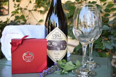 wineglasses with a bottle of wine, givt certificate, and a spa towel