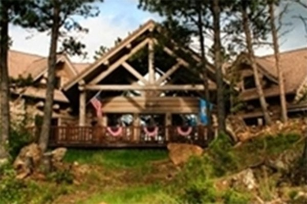 Log cabin on hilltop amongst trees