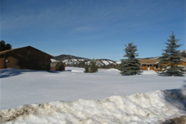Field of snow between log cabins