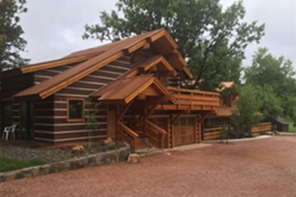 Wood cabin with large dirt parking lot