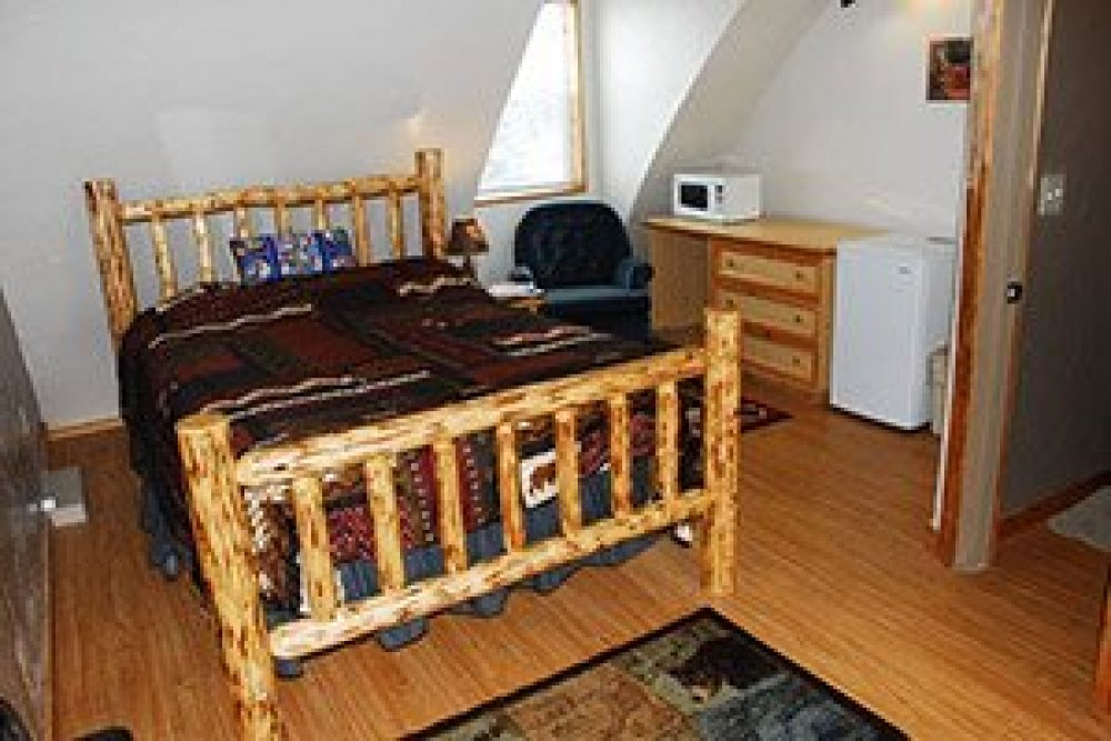 A bed carved from logs with nearby minifridge and microwave