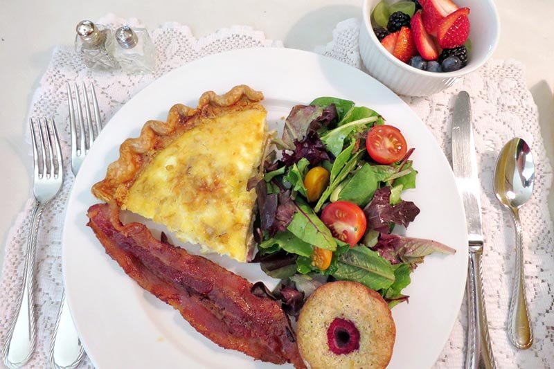 Breakfast quiche salad bacon toast juice fruit