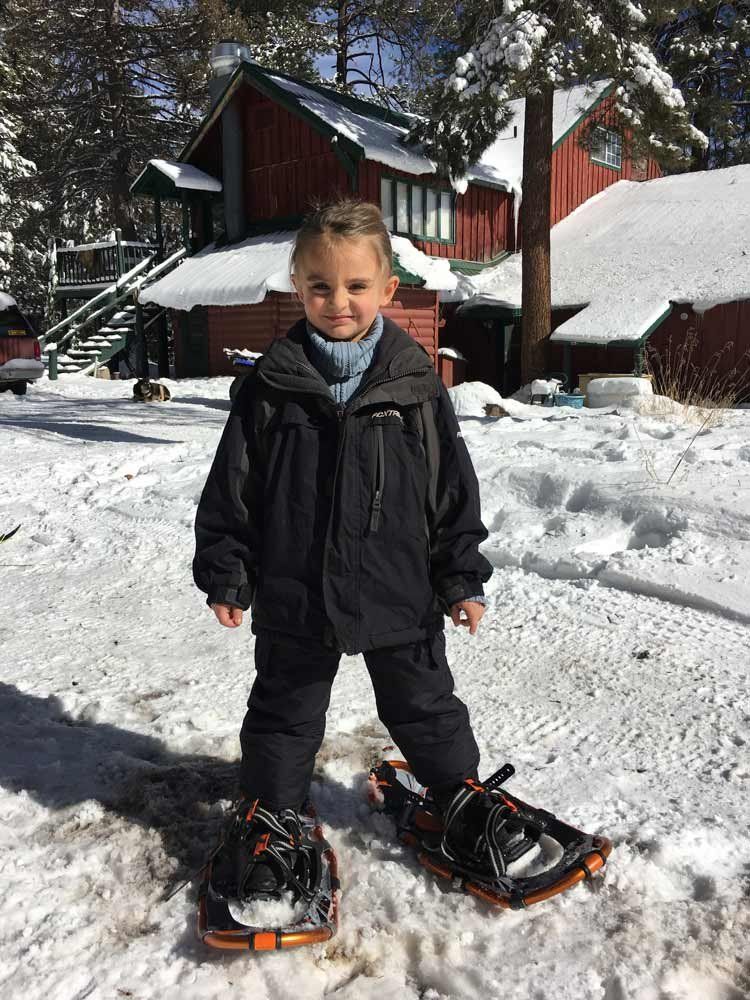A child wearing snowshoes