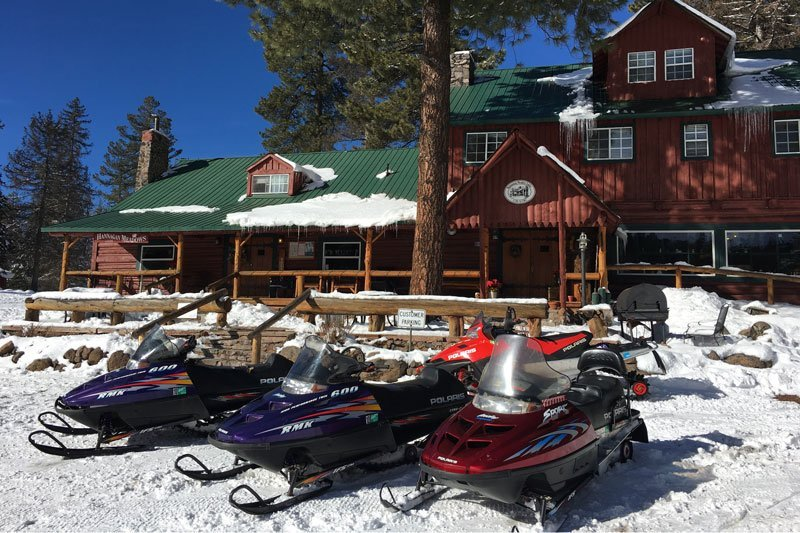 Snowmobiles parked in front of a lodge