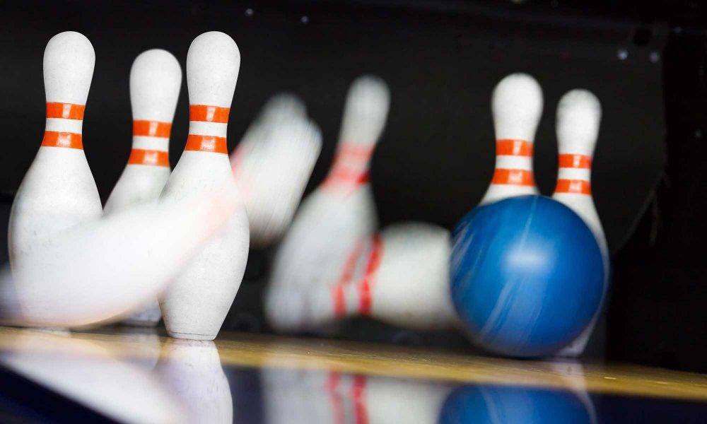 A bowling ball knocking down pins