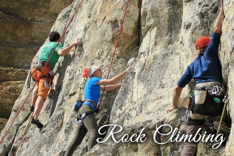 Three people rock climbing