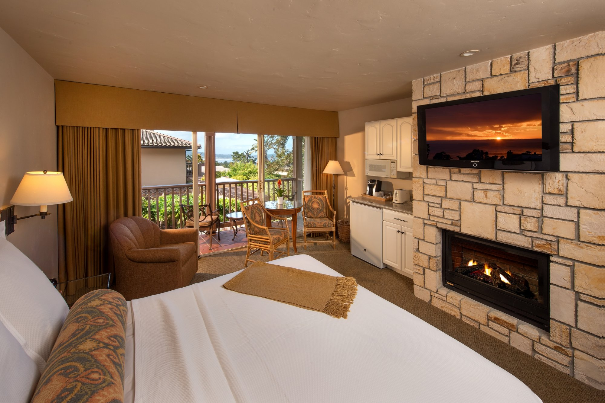 Bed facing fireplace with balcony and Ocean View