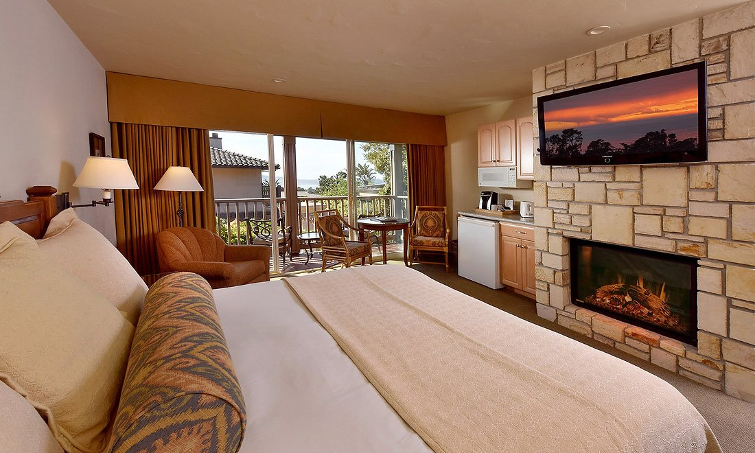 A bed facing a fireplace and television