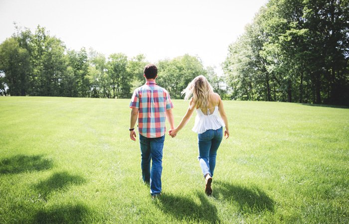 White Birch Inn couple holding hands walking through grass - Photo by Colin Maynard on Unsplash