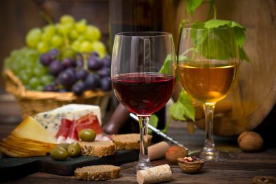 red and white wines in front of plate of cheese and grapes