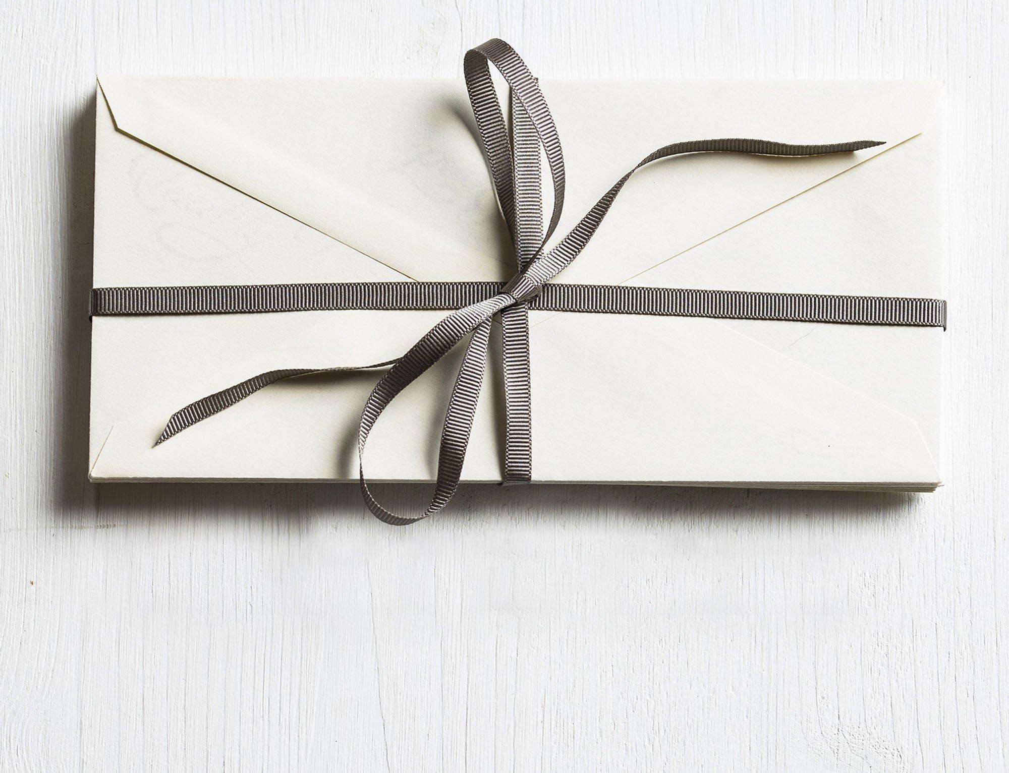 white envelop wrapped with grey ribbon