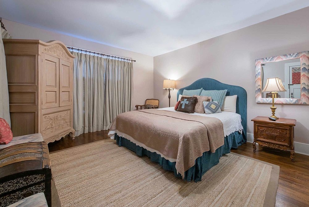 bed with armoire and curtained window