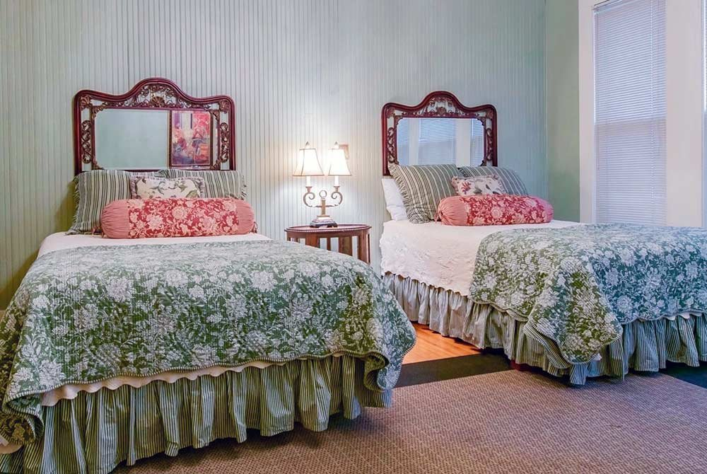 two beds with lamp in the middle