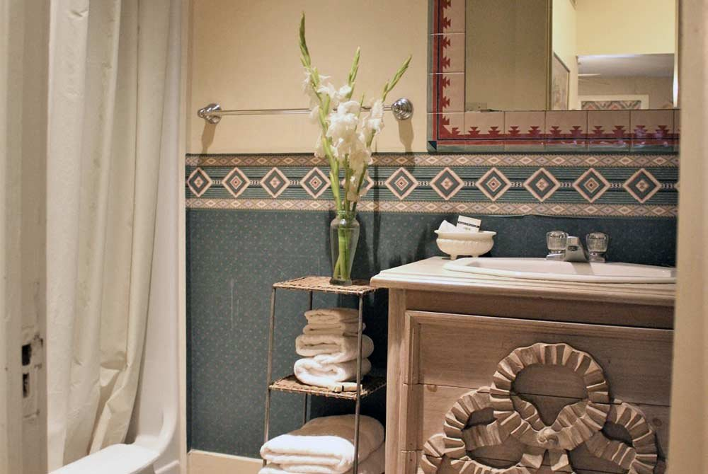 bathroom with shower, sink and linens