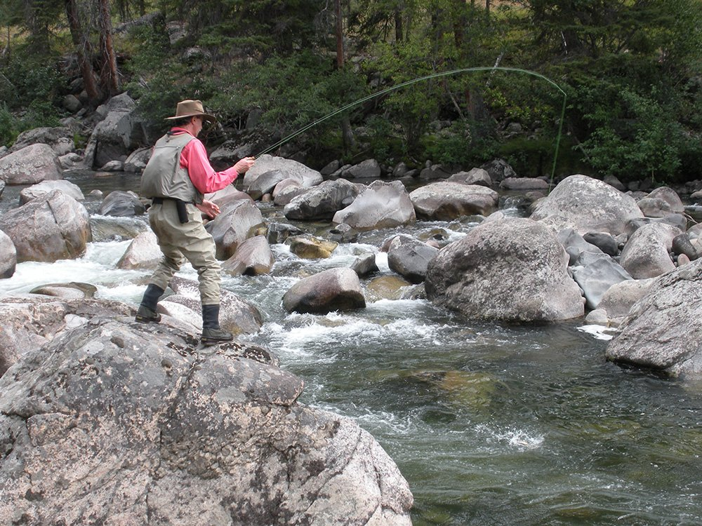 man in fishing vest fly fishing on a river