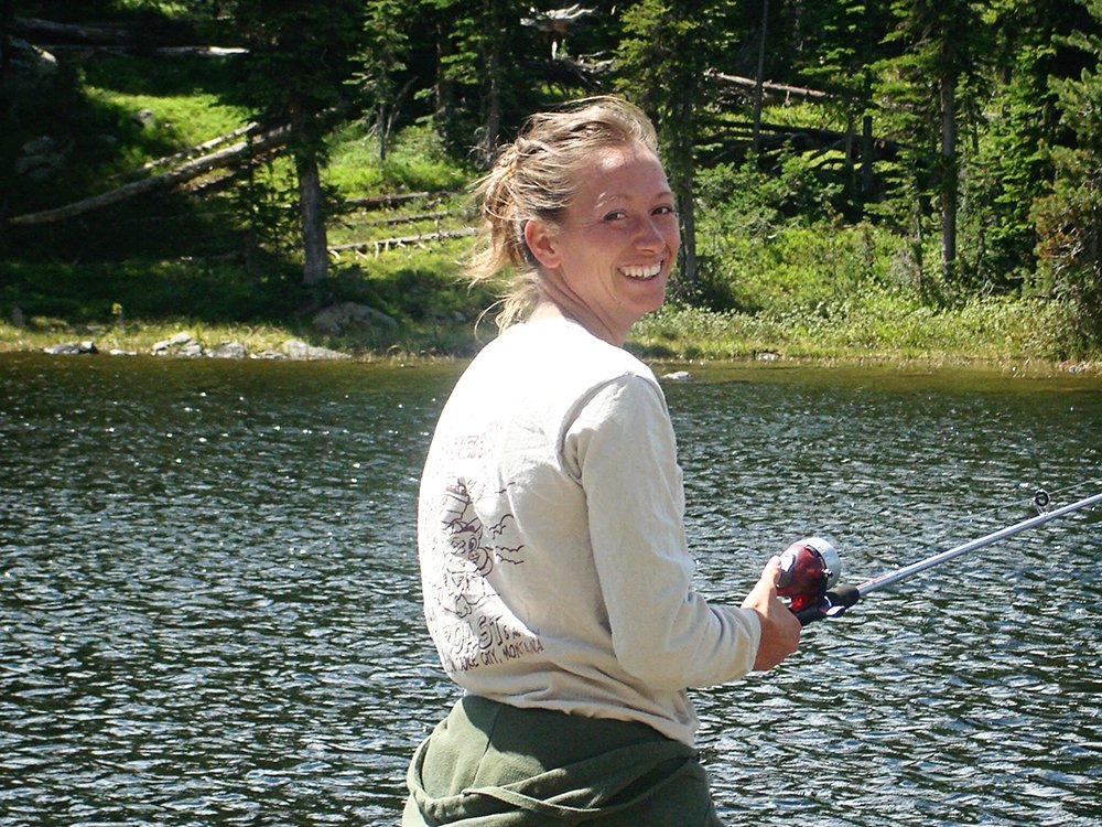 woman looking over her shoulder while fishing on a lake