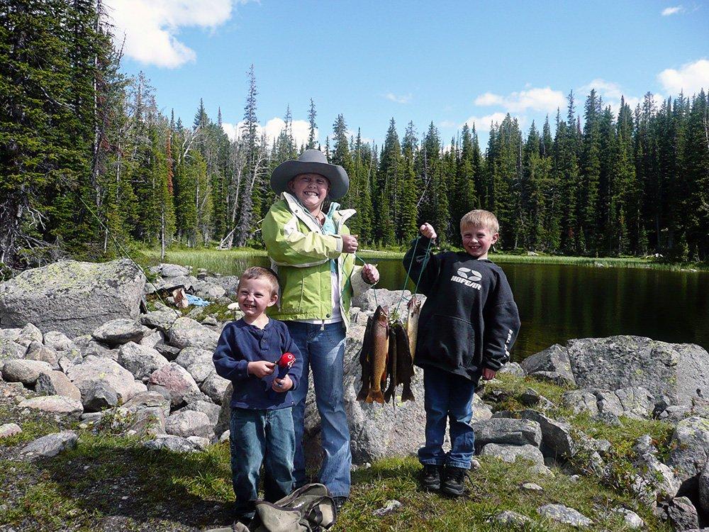 three children holding up fish next to tree lined lake